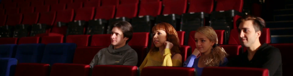 four-people-sitting-in-the-seats-of-cinema-theater